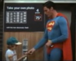 Superman gives his picture to the boy who just paid at the photo booth.
