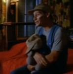 Ernest holds a stuffed animal while singing about his sorrows.